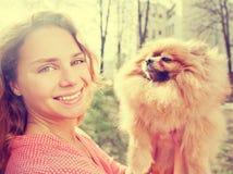 Le petit chien de Pomeranian et joli jouer de femme extérieurs Photos libres de droits