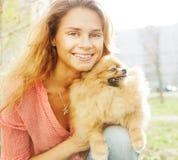 Le petit chien de Pomeranian et joli jouer de femme extérieurs Images stock