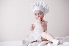 Le petit cuisinier mignon mange la tomate Photographie stock libre de droits