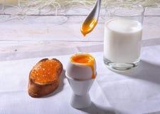 Le petit déjeuner de matin a placé avec l'oeuf, la confiture d'oranges sur le pain grillé de pain et le lait en verre Image stock