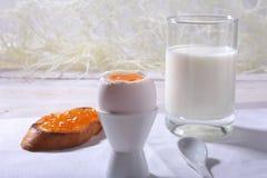 Le petit déjeuner de matin a placé avec l'oeuf, la confiture d'oranges sur le pain grillé de pain et le lait en verre Images libres de droits