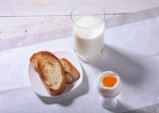 Le petit déjeuner de matin a placé avec l'oeuf, la confiture d'oranges sur le pain grillé de pain et le lait en verre Photographie stock libre de droits