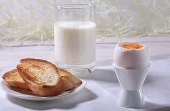 Le petit déjeuner de matin a placé avec l'oeuf, la confiture d'oranges sur le pain grillé de pain et le lait en verre Photographie stock