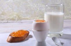 Le petit déjeuner de matin a placé avec l'oeuf, la confiture d'oranges sur le pain grillé de pain et le lait en verre Images stock