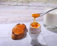 Le petit déjeuner de matin a placé avec l'oeuf, la confiture d'oranges sur le pain grillé de pain et le lait en verre Photo libre de droits