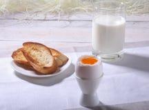 Le petit déjeuner de matin a placé avec l'oeuf, la confiture d'oranges sur le pain grillé de pain et le lait en verre Image libre de droits