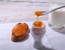 Le petit déjeuner de matin a placé avec l'oeuf, la confiture d'oranges sur le pain grillé de pain et le lait en verre Photos libres de droits