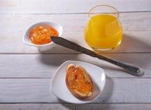 Le petit déjeuner de matin a placé avec la confiture d'oranges sur le pain grillé et le jus de pain en verre Photo libre de droits