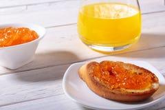 Le petit déjeuner de matin a placé avec la confiture d'oranges sur le pain grillé et le jus de pain en verre Photos libres de droits