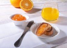 Le petit déjeuner de matin a placé avec la confiture d'oranges sur le pain grillé et le jus de pain en verre Image libre de droits