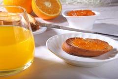 Le petit déjeuner de matin a placé avec la confiture d'oranges sur le pain grillé et le jus de pain en verre Photographie stock