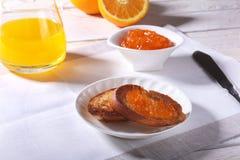 Le petit déjeuner de matin a placé avec la confiture d'oranges sur le pain grillé et le jus de pain en verre Images libres de droits