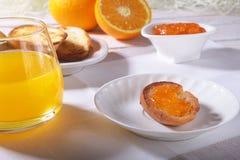 Le petit déjeuner de matin a placé avec la confiture d'oranges sur le pain grillé et le jus de pain en verre Photos stock