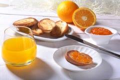 Le petit déjeuner de matin a placé avec la confiture d'oranges sur le pain grillé et le jus de pain en verre Images stock