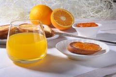 Le petit déjeuner de matin a placé avec la confiture d'oranges sur le pain grillé et le jus de pain en verre Photo stock