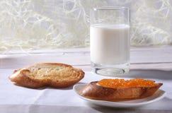 Le petit déjeuner de matin a placé avec la confiture d'oranges sur le pain grillé et le lait de pain en verre Image stock