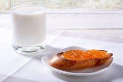Le petit déjeuner de matin a placé avec la confiture d'oranges sur le pain grillé et le lait de pain en verre Images stock