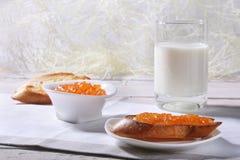 Le petit déjeuner de matin a placé avec la confiture d'oranges sur le pain grillé et le lait de pain en verre Images libres de droits