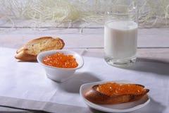 Le petit déjeuner de matin a placé avec la confiture d'oranges sur le pain grillé et le lait de pain en verre Photographie stock