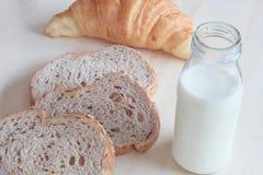 Le petit déjeuner a placé avec du lait et le croissant de pain de blé entier photo libre de droits