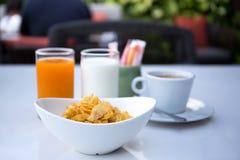 Le petit déjeuner a placé avec les cornflakes et la tasse de café Photos stock