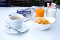 Le petit déjeuner a placé avec les cornflakes et la tasse de café et de jus d'orange Images libres de droits