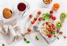 Le petit déjeuner sain avec le gruau de farine d'avoine, fraise, écrous, bloquent a Image stock