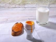 Le petit déjeuner sain de matin a placé avec l'oeuf, la confiture d'oranges sur le pain grillé de pain et le lait en verre Images stock
