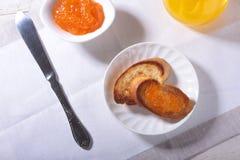 Le petit déjeuner sain de matin a placé avec la confiture d'oranges sur le pain grillé et le jus de pain en verre Photo stock