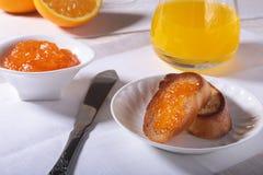 Le petit déjeuner sain de matin a placé avec la confiture d'oranges sur le pain grillé et le jus de pain en verre Photos libres de droits