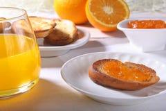 Le petit déjeuner sain de matin a placé avec la confiture d'oranges sur le pain grillé et le jus de pain en verre Images libres de droits