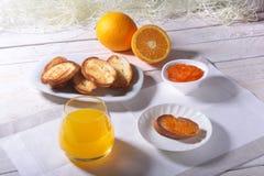 Le petit déjeuner sain de matin a placé avec la confiture d'oranges sur le pain grillé et le jus de pain en verre Photo libre de droits
