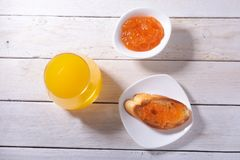 Le petit déjeuner sain de matin a placé avec la confiture d'oranges sur le pain grillé et le jus de pain en verre Images stock