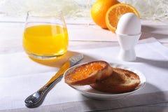 Le petit déjeuner sain de matin a placé avec la confiture d'oranges sur le pain grillé, l'oeuf et le jus de pain en verre Photographie stock