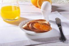 Le petit déjeuner sain de matin a placé avec la confiture d'oranges sur le pain grillé, l'oeuf et le jus de pain en verre Photos stock