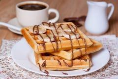Le petit déjeuner waffles avec les bananes, le sirop de chocolat et le café Images libres de droits
