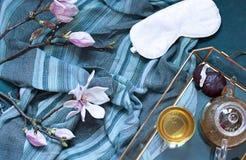 Le petit d?jeuner dans l'appartement de lit s'?tendent avec les fleurs de magnolia et le th? vert avec des guimauves Concept de p photographie stock