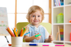 Le petit dessin mignon d'enfant d'élève du cours préparatoire avec le feutre parquent à la maison Photographie stock libre de droits
