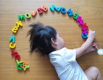Le petit dessus d'enfant en bas âge regardent vers le bas avec ses jouets Image libre de droits