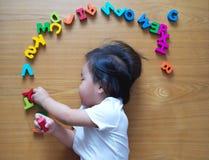 Le petit dessus d'enfant en bas âge regardent vers le bas avec ses jouets Images stock