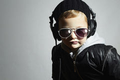 Le petit DJ garçon drôle dans les lunettes de soleil et des écouteurs Musique de écoute d'enfant dans des écouteurs disc-jockey photo libre de droits