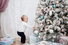 Le petit enfant accroche des boules de Noël sur l'arbre Photographie stock libre de droits
