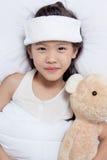 Le petit enfant asiatique a la fièvre et en s'étendant sur le lit, obtenez bien photo stock