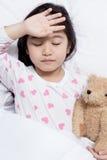 Le petit enfant asiatique a la fièvre et la pose sur le lit image libre de droits