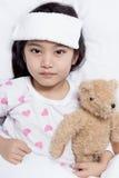 Le petit enfant asiatique a la fièvre et la pose sur le lit images stock