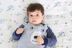 Le petit enfant attirant avec les cheveux foncés et observe, utilise des pyjamas, regarde directement dans l'appareil-photo tandi photo libre de droits
