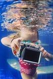 Le petit enfant avec l'appareil-photo prend la photo sous-marine dans la piscine image stock