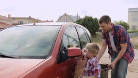 Le petit enfant blond l lave le phare de la voiture sous le gardien de son mouvement lent de jeune père banque de vidéos