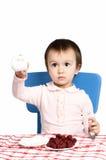Le petit enfant boit du lait avec des framboises Photographie stock