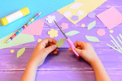 Le petit enfant crée une carte de voeux pour la maman opération L'enfant tient des ciseaux dans des ses mains et coupe une feuill Images libres de droits